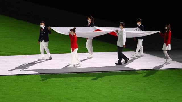 La bandera de Japón portada por los voluntarios de Tokio 2020.
