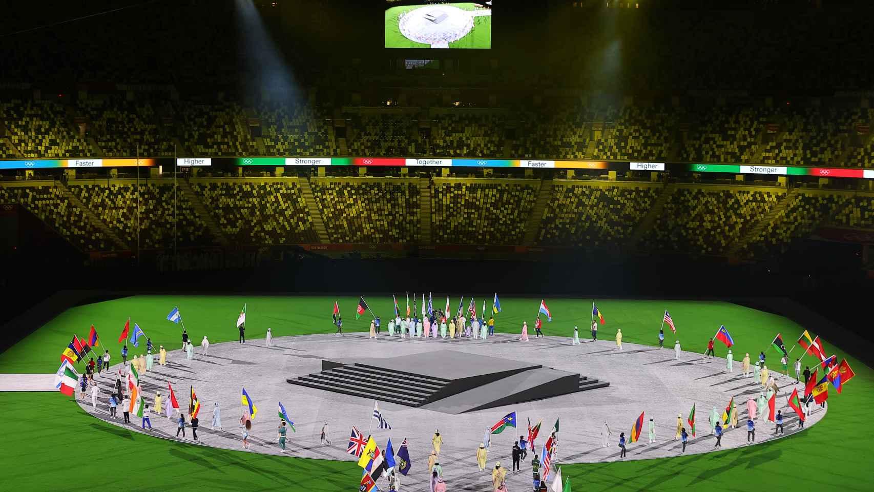 Las banderas de cada país colocándose en el centro del estadio de Tokio 2020