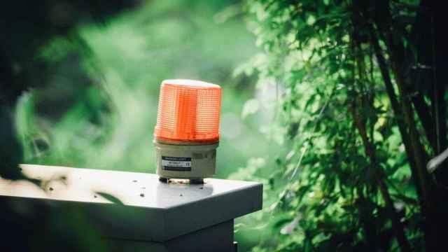 Una luz roja de emergencia, en un entorno natural. Foto: Lucas Law / Unsplash.