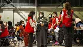 Una trabajadora de Cruz Roja conversa con una de las mujeres repatriadas en el campamento de Torrejón de Ardoz.