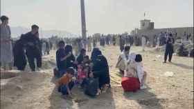 Afganos esperan en las inmediaciones del aeropuerto.