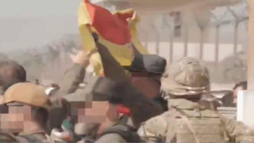 Un miembro de los GEO agita una bandera española en el exterior del aeropuerto de Kabul para llamar la atención de los colaboradores de la embajada.