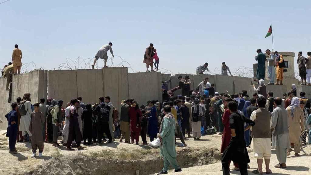 Afganos se agolpan a lo largo del muro del aeropuerto internacional Hamid Karzai, en Kabul. Efe