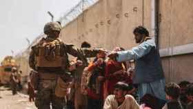 Un marine ofrece botellas de agua a los evacuados en Kabul, en el aeropuerto Hamid Karzai.