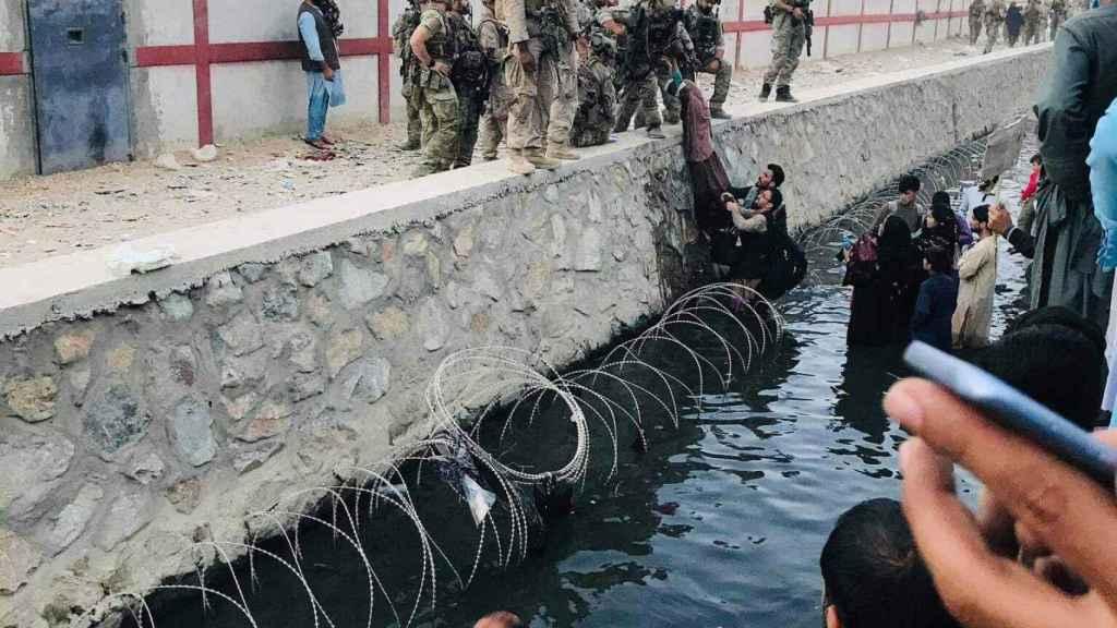 Varios afganos sortean el foto de agua que rodea un lateral del aeropuerto de Kabul, para huir del país.