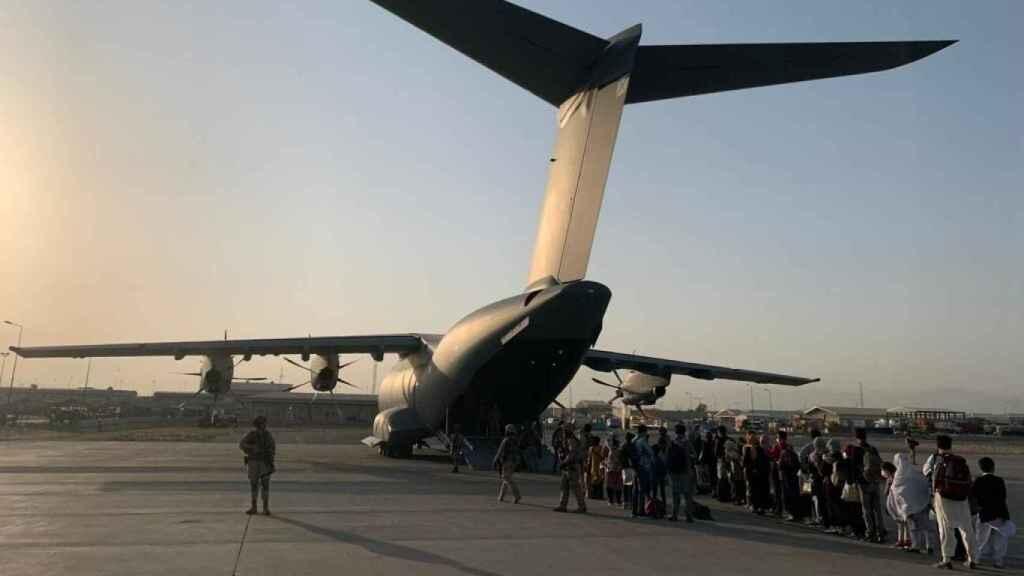 Un grupo de refugiados afganos embarca en un avión A400M del Ejército español en el aeropuerto de Kabul.