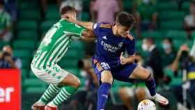 Miguel Gutiérrez, evita la presión de un jugador del Real Betis