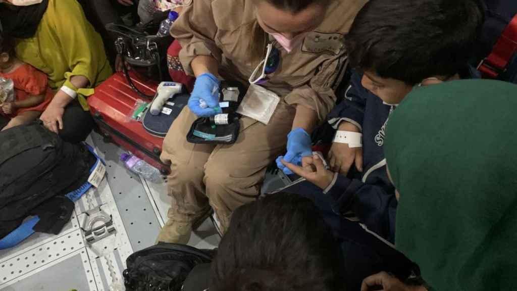 Una sanitaria militar atiende a un niño diabético con una crisis de hipoglucemia.