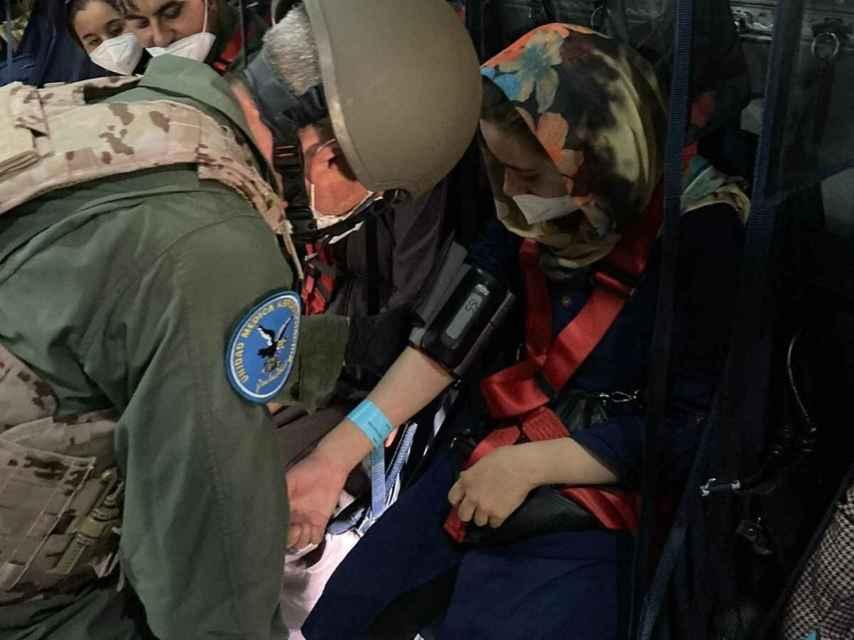 Los sanitarios militares atienden a una mujer afgana en un vuelo de evacuación.
