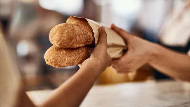 Imagen de archivo de una mujer comprando pan.