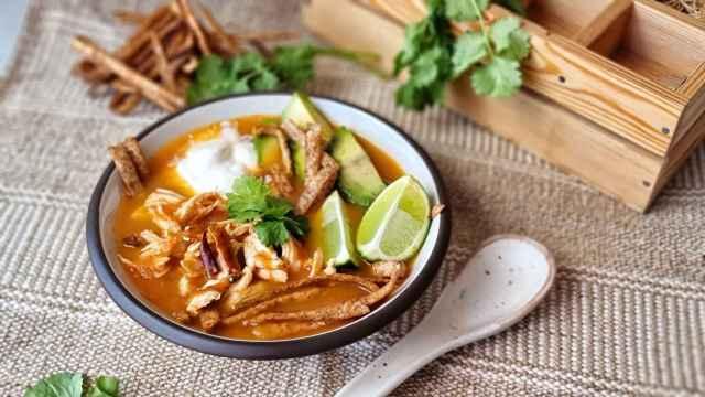 Sopa mexicana de tortilla o sopa azteca con aguacate y pollo