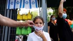 Una joven de 12 años apunto de recibir su vacuna en Israel.