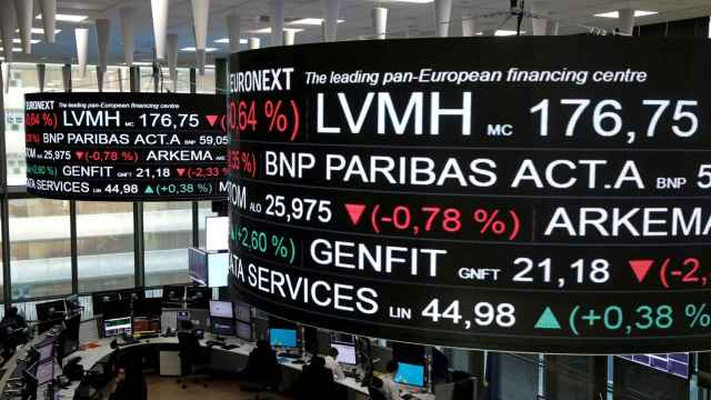 FILE PHOTO: Company stock price information, including that for LVMH Moet Hennessy Louis Vuitton SA, is displayed on screens as they hang above the Paris stock exchange, operated by Euronext NV, in La Defense business district in Paris