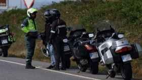 Un agente de la Guardia Civil dialoga con dos motoristas en la carretera.