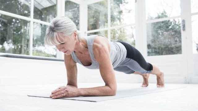 Una mujer realiza una plancha en el gimnasio.