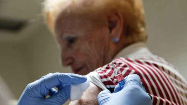 Una mujer recibe una vacuna contra la gripe.
