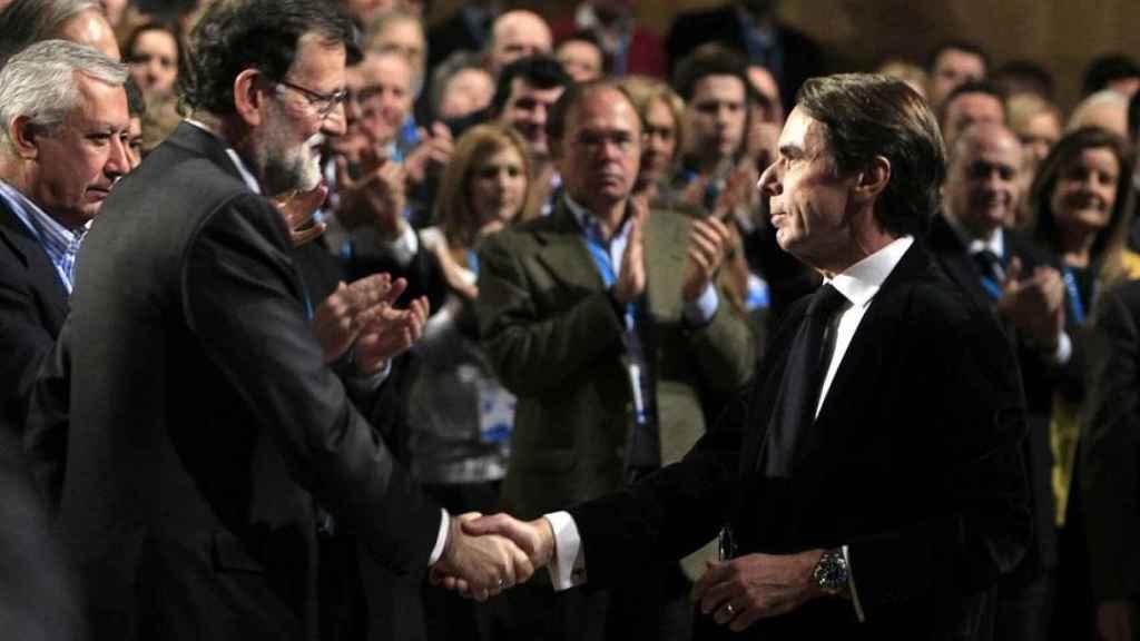 Mariano Rajoy y José María Aznar se saludan en la convención del PP, en 2015.