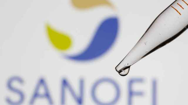 A test tube is seen in front of a displayed Sanofi logo in this illustration