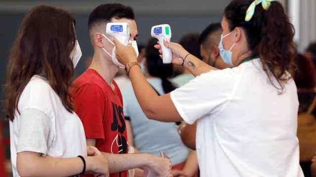 Una sanitaria toma la temperatura de dos jóvenes en Alicante.