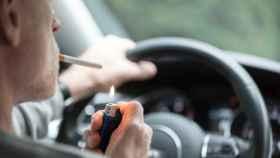 Conductor encendiendo un cigarrillo al volante