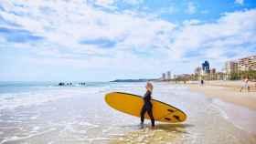 Una surfista en la playa de San Juan de Alicante.