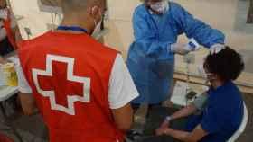 Cruz Roja Alicante atiende a un inmigrante en una llegada de patera a la costa en julio de este año.