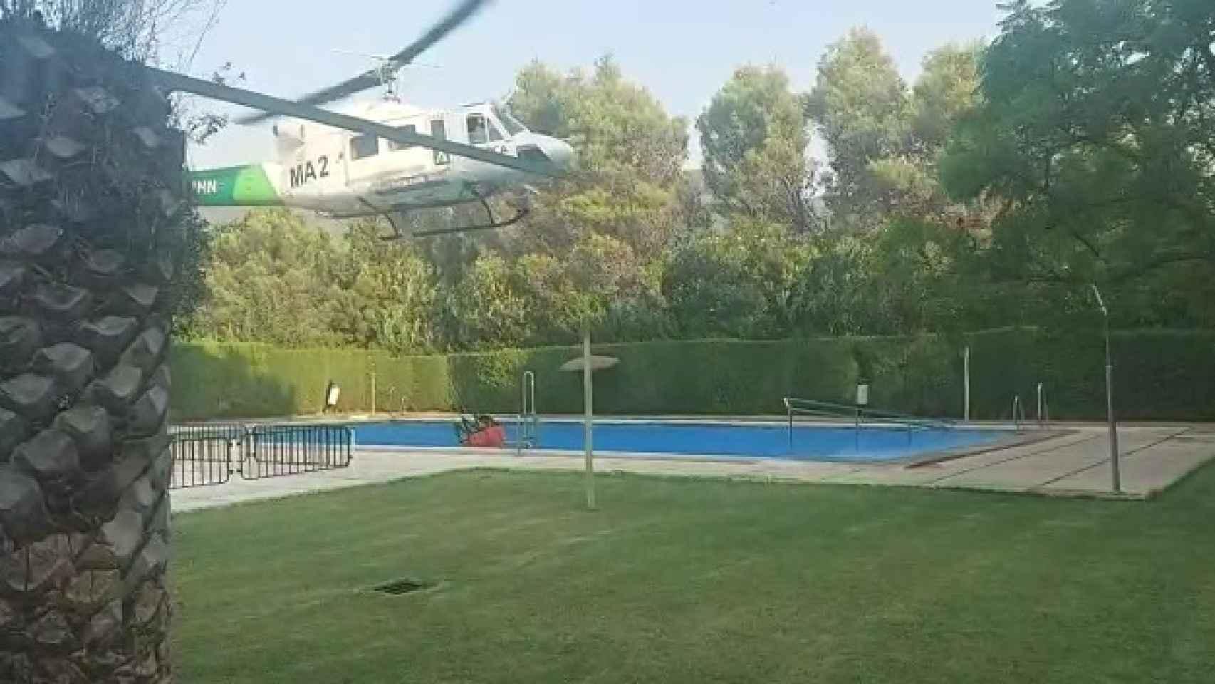 Así carga agua uno de los helicópteros que participan en la extinción del incendio de Sierra Bermeja.