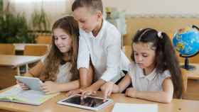 Estudiantes en clase usando libros y tabletas.