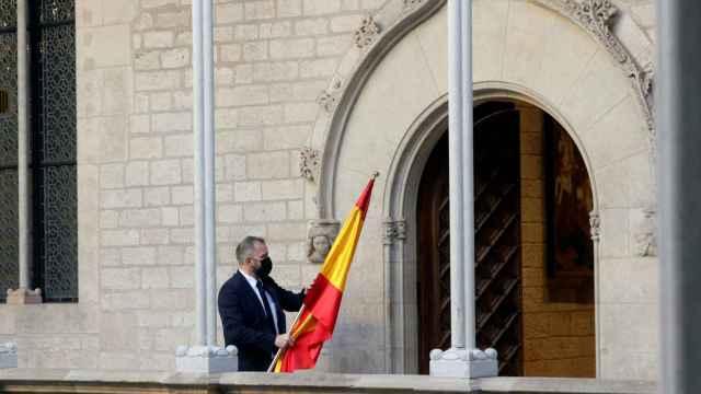 Un ujier se lleva la bandera española de la Galería Gótica del Palau de la Generalitat tras la comparecencia de Pedro Sánchez.