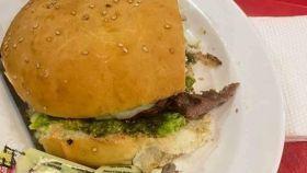 La hamburguesa en cuestión con el dedo en el plato.