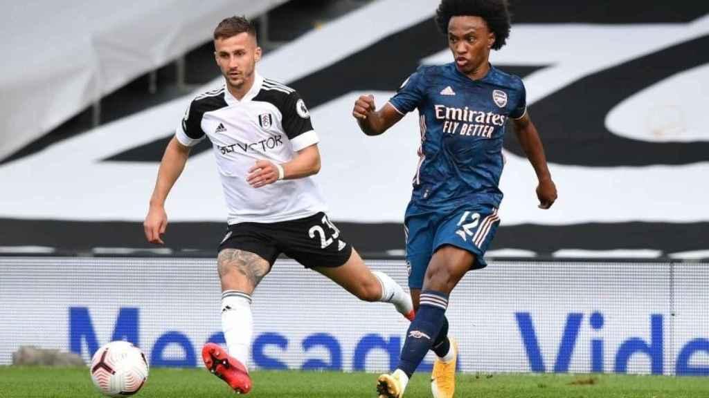 Joe Bryan en acción con Willian durante un Fulham - Arsenal