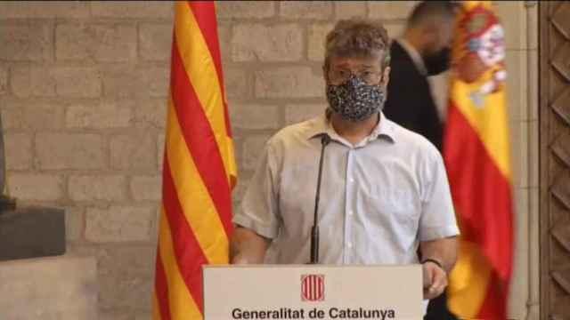 Un funcionario retira la bandera de España tras la comparecencia de Pedro Sánchez