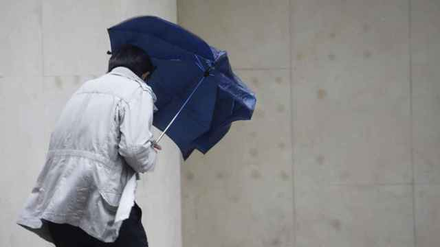Un hombre se protege con un paraguas de la lluvia y el viento.