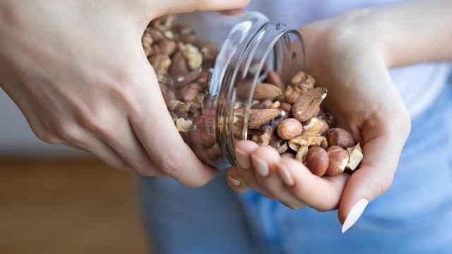 Una persona toma un puñado de frutos secos variados.
