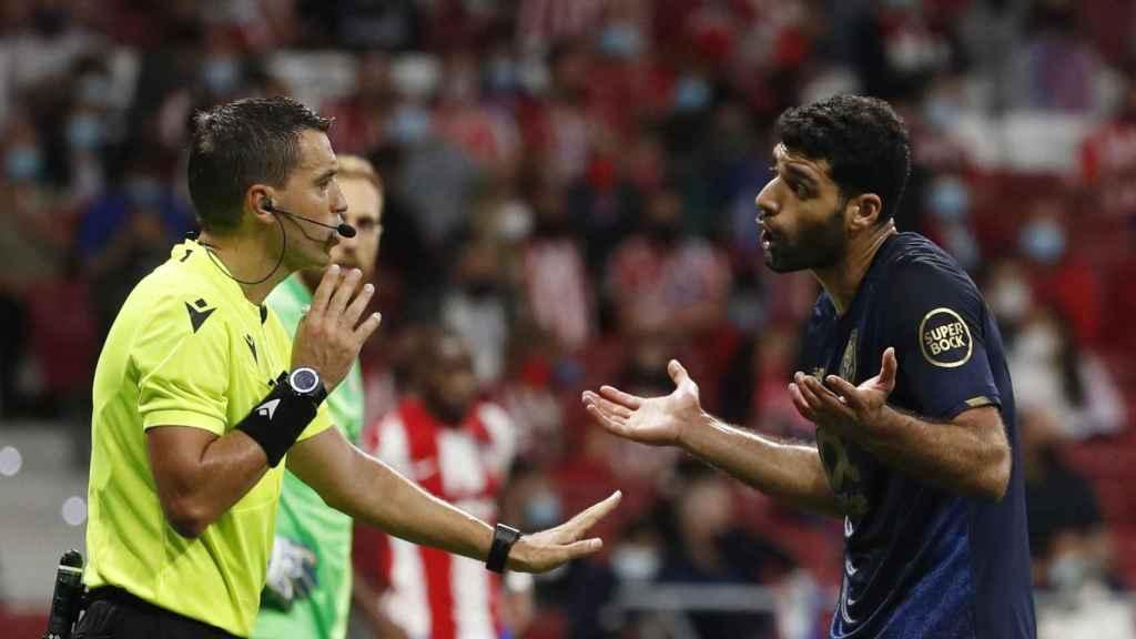 El árbitro Hategan hablando con Mehdi en el Atleti - Oporto