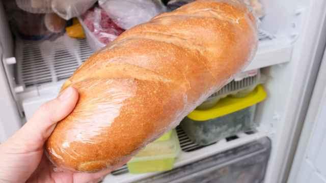 Una persona coloca una barra de pan en el interior del congelador.