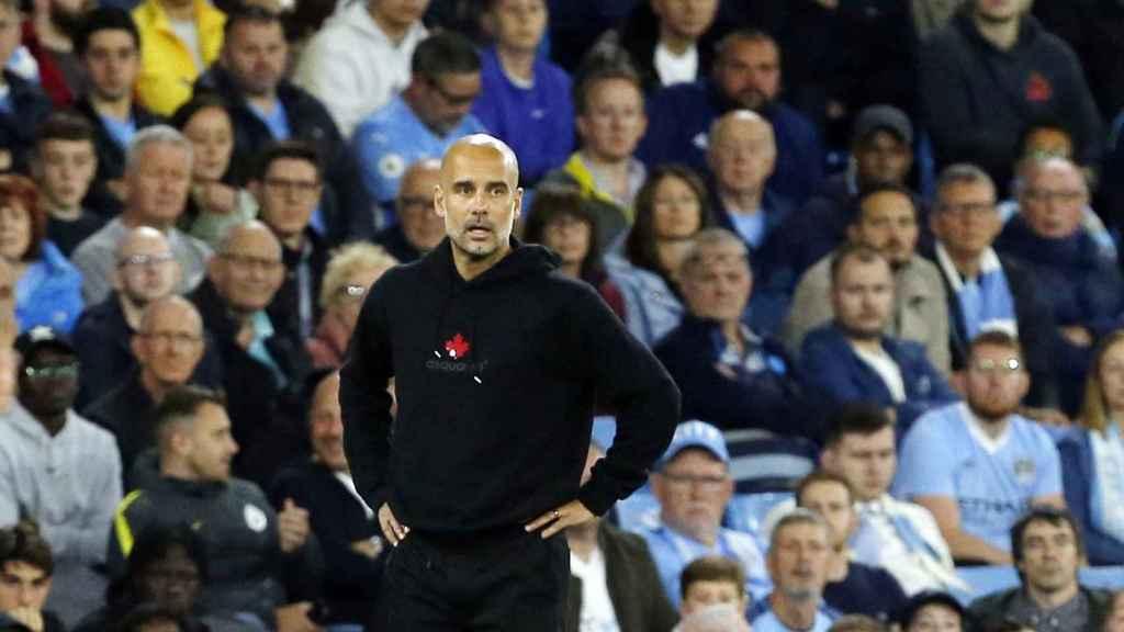 Guardiola, brazos en jarra ante la afición del Manchester City
