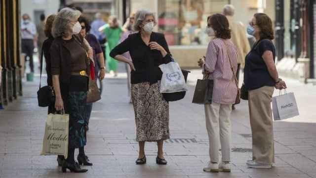 Un grupo de mujeres conversa en una calle de Sevilla con las mascarillas puestas. EFE