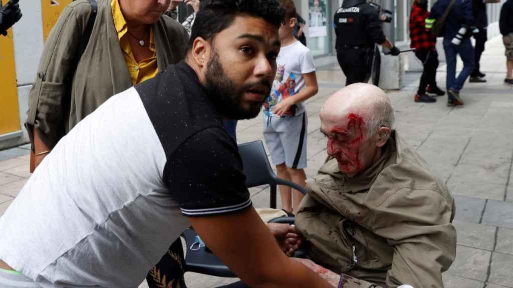 Un hombre es atendido tras resultar herido durante los disturbios.