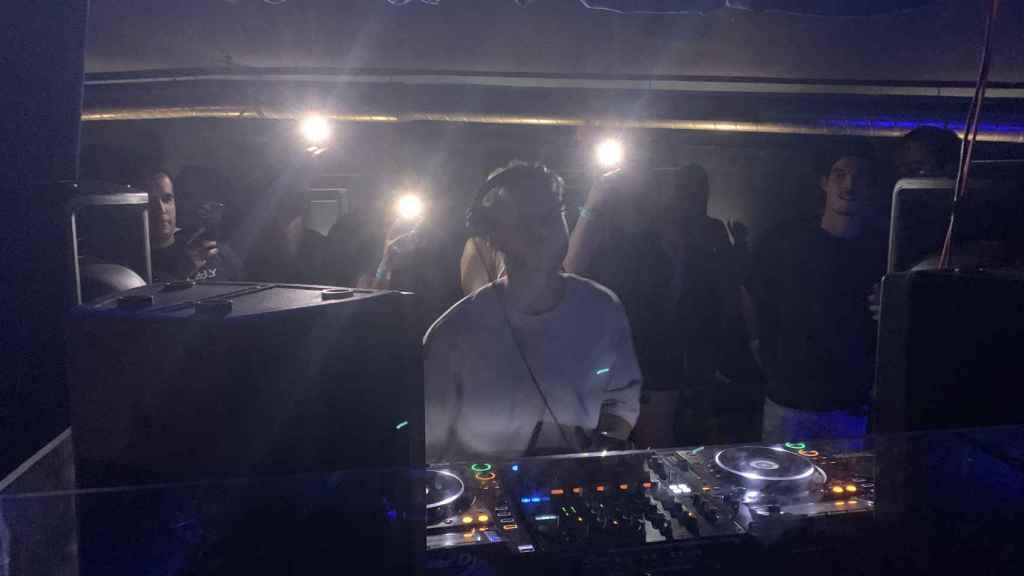 Un DJ pincha música electrónica en una discoteca. Tras él, un reservado abarrotado.