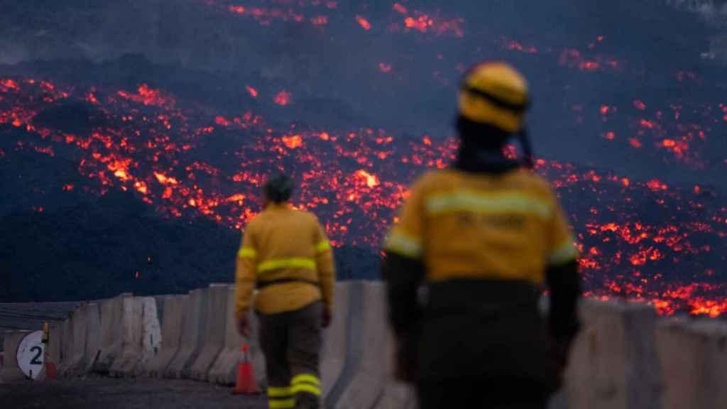 Dos bomberos, frente a las lenguas de lava.