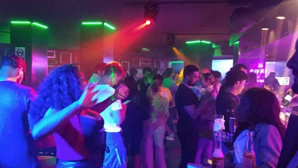 Un grupo de personas bailando en la pista de una discoteca pese a estar prohibido.