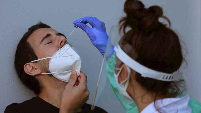 Una sanitaria realiza una prueba PCR a un joven
