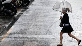 Uan mujer sostiene un paraguas mientras llueve.