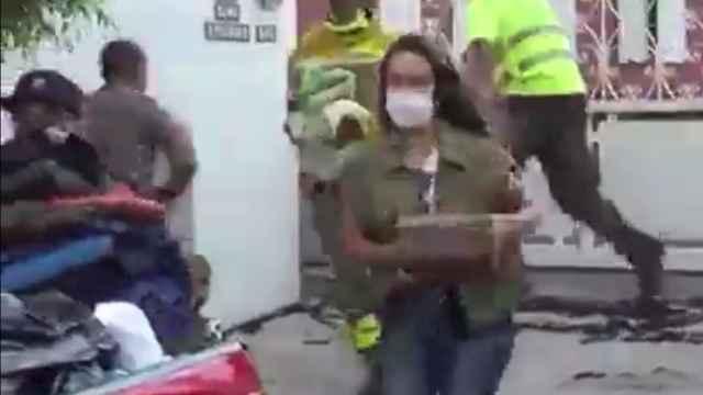 La reportera cargando objetos de la familia afectada.