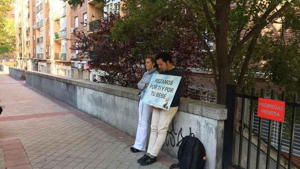 Dos jóvenes sostienen un cartel frente a la clínica Dator de Madrid.