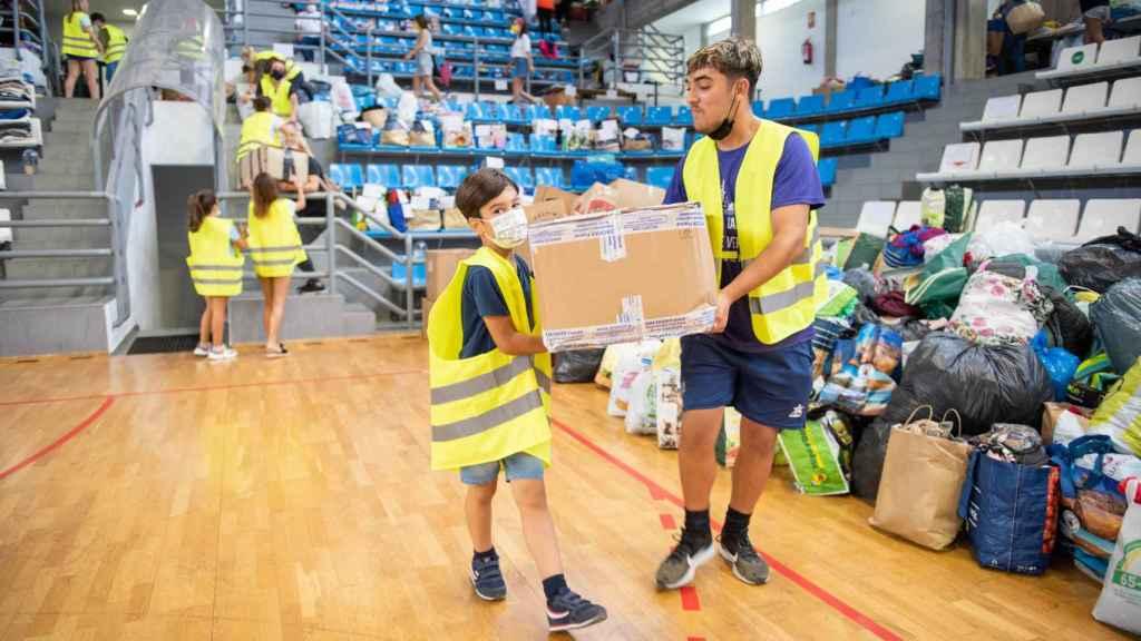 Noah y Fabián ayudan con las donaciones que llegan al pabellón.