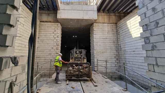 Varios operarios trasladan parte de los restos arqueológicos del Metro de Málaga.