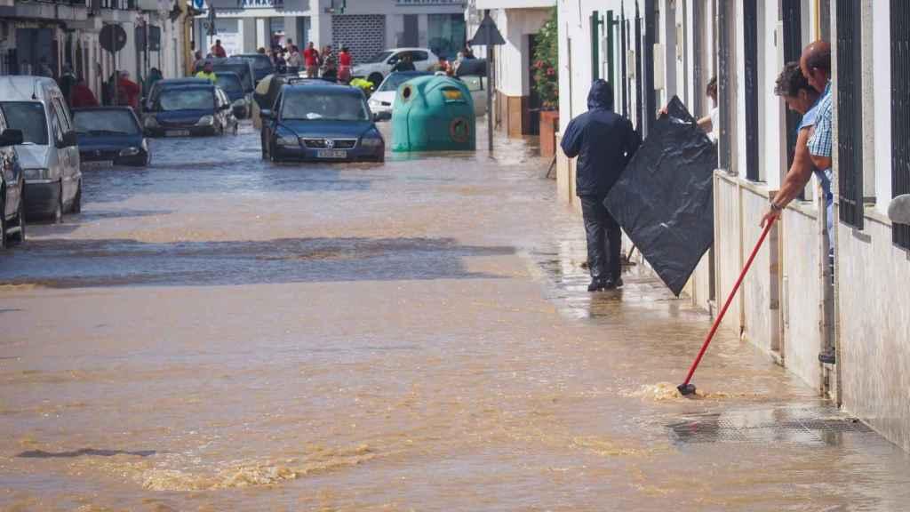 Vecinos de Lepe (Huelva) observando el nivel de agua en una calle inundada.