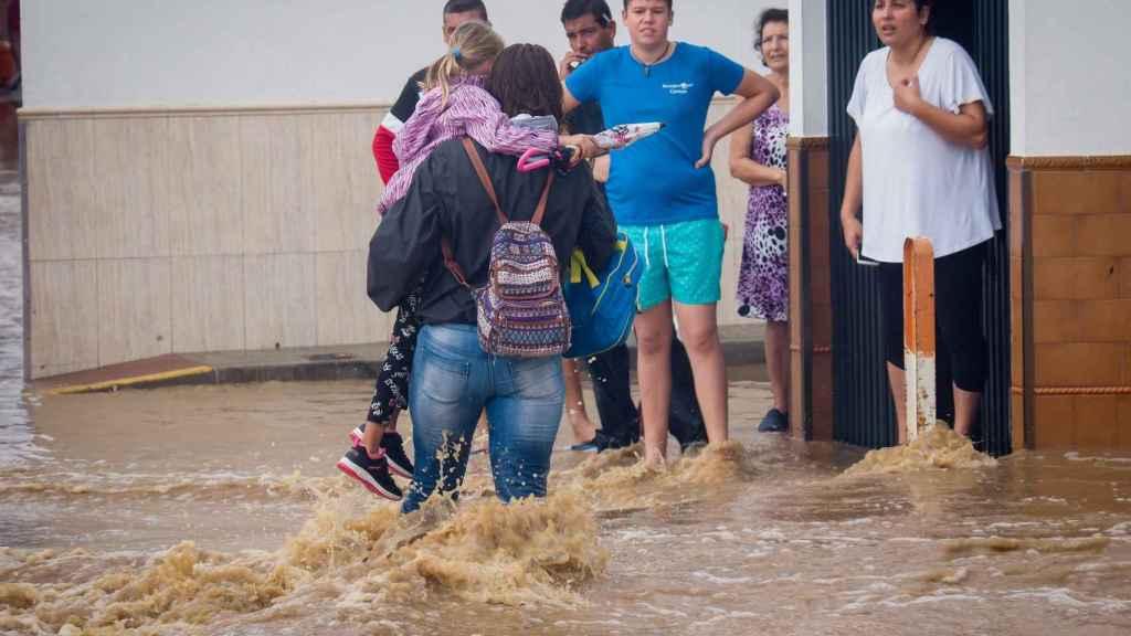 Vecinos de Lepe (Huelva) observan a una mujer con una niña en brazos cruzando una calle inundada tras las fuertes lluvias.